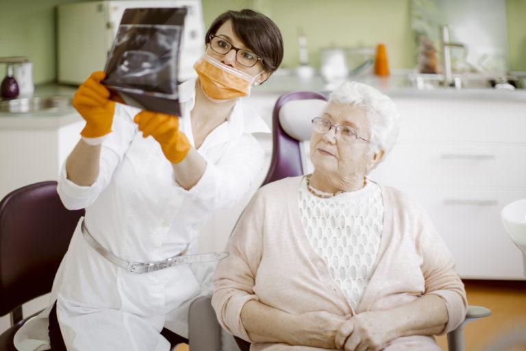 Стоматолог рассказывает пациенту об отличиях базальной имплантации от all on 4