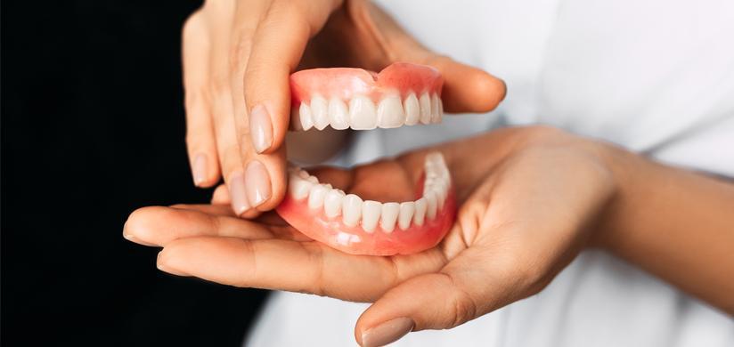 Снятый зубной протез в руках