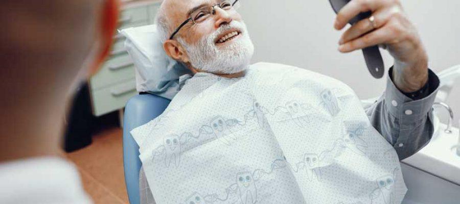 Пациент смотрит в зеркало после установки зубного протеза без неба