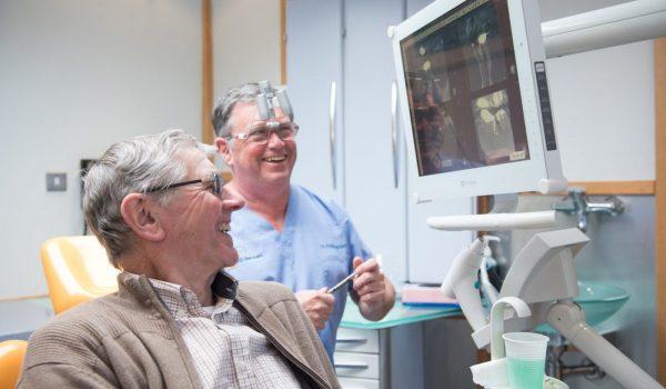 Доктор и пациент изучают снимок одного зуба